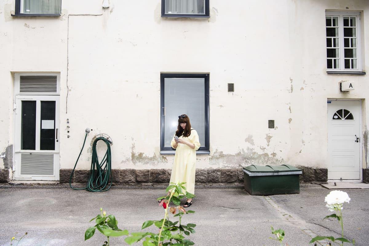 Pauliina Saares keltaisessa kesämekossa töölöläisen talon sisäpihalla.