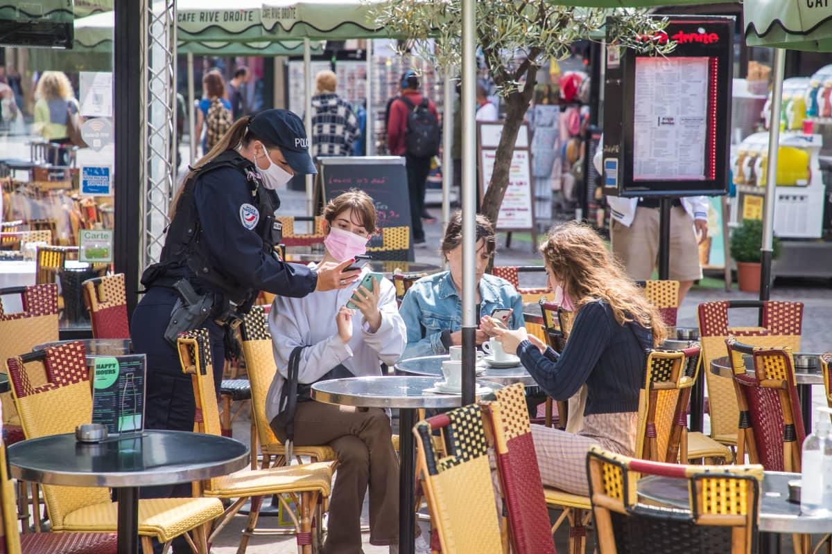 Poliisi tarkasti asiakkaiden koronapasseja pariisilaiskahvilassa maanantaina.