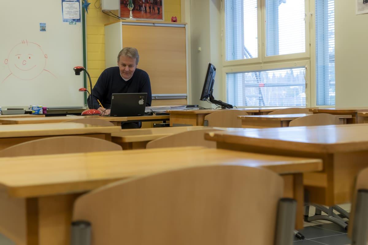 Luokanvalvoja Juhani Haapajoki istuu tyhjässä luokkahuoneessa ja pitää oppituntia verkon kautta