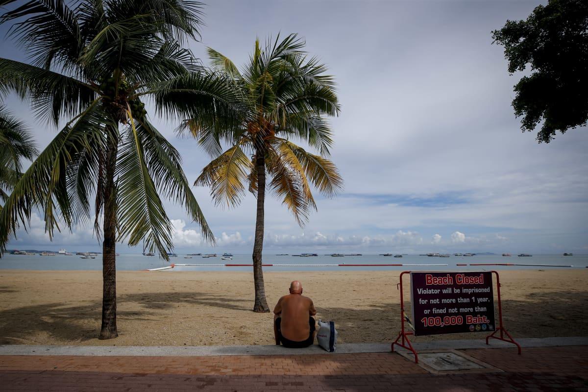 Mies istuu rannalla Thaimaassa