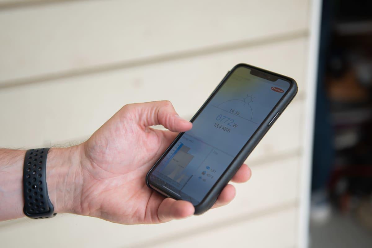Petri Aho tarkastelee aurinkopaneelien toimintaa ja hyötyjä älypuhelimen sovelluksesta.
