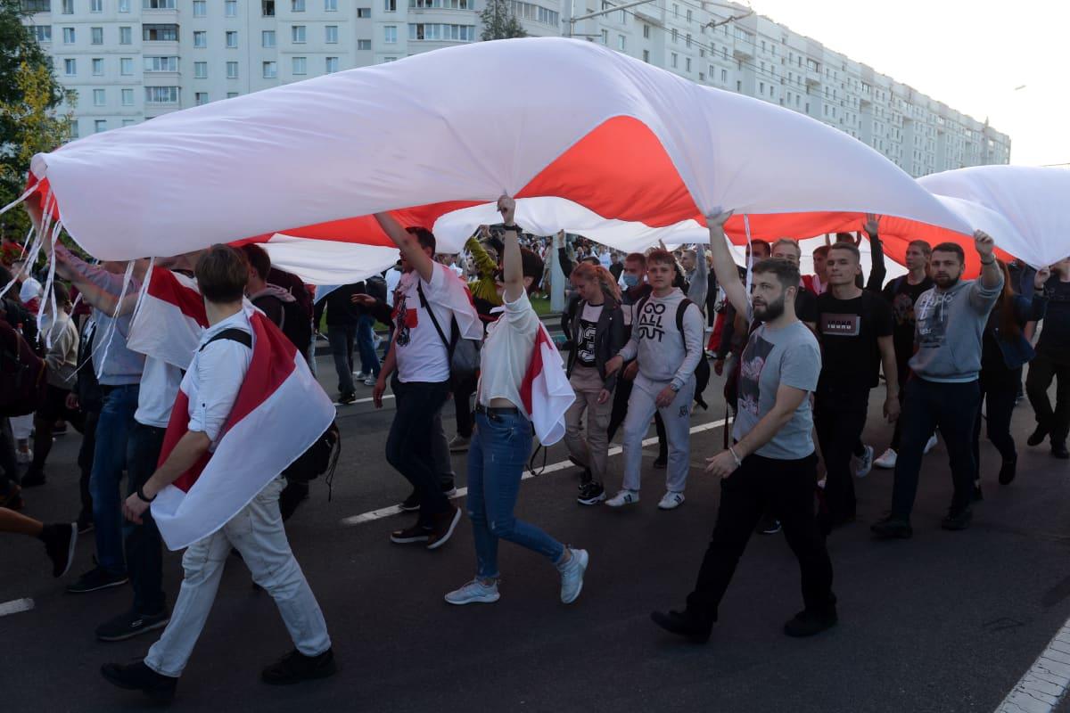 Mielenosoittajat kantavat valtavaa valko-punaista lippua päidensä päällä