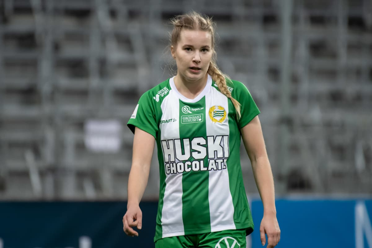 Eva Nyström katsoo kameraan pelikentällä vihreässä paidassaan.