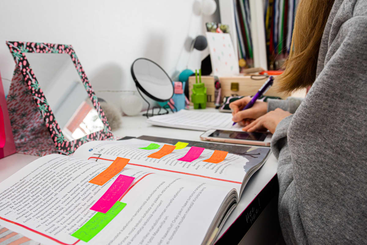 Yläkouluikäinen tyttö opiskelee etänä.