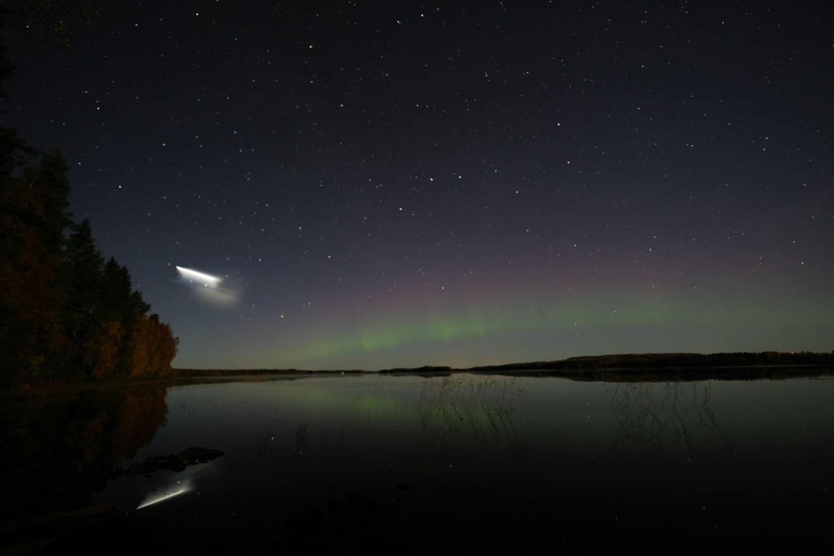 Kuva öisestä tähtitaivaasta järvenrannasta otettuna. Vastarannan yllä näkyy revontulia, ja vasemmalla taivaalla kummallinen vaalea valoilmiö.
