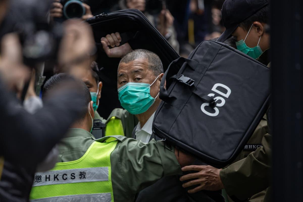 Jimmy Laita kuljetetaan viranomaisten keskellä. Hänellä on kasvoillaan suojamaski.