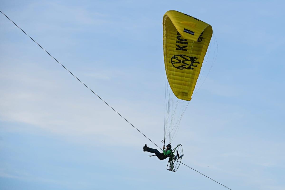 Greenpeace-aktivisti lentää moottoroidulla varjoliidolla.