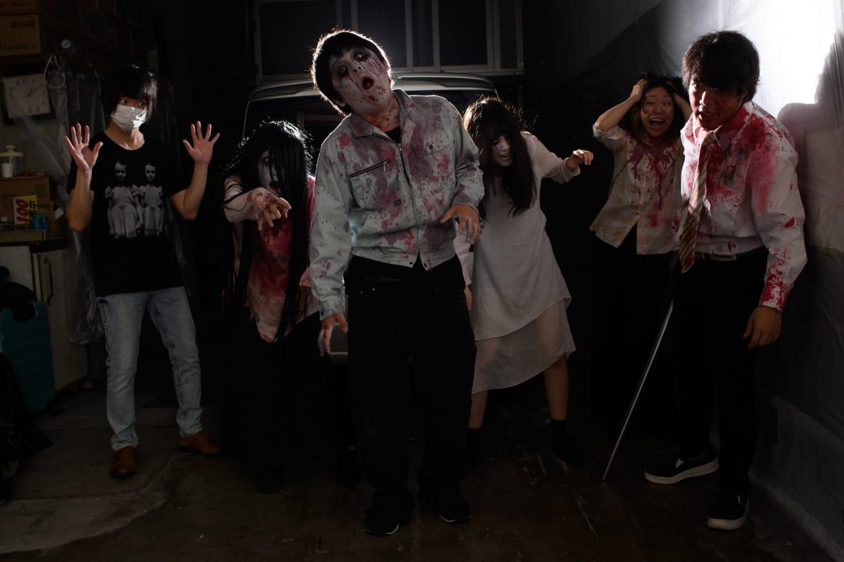 Pelokkaita asiakkaita zombeja esittävien näyttelijöiden keskellä japanilaisessa drive-in-kummitustalossa Tokiossa.