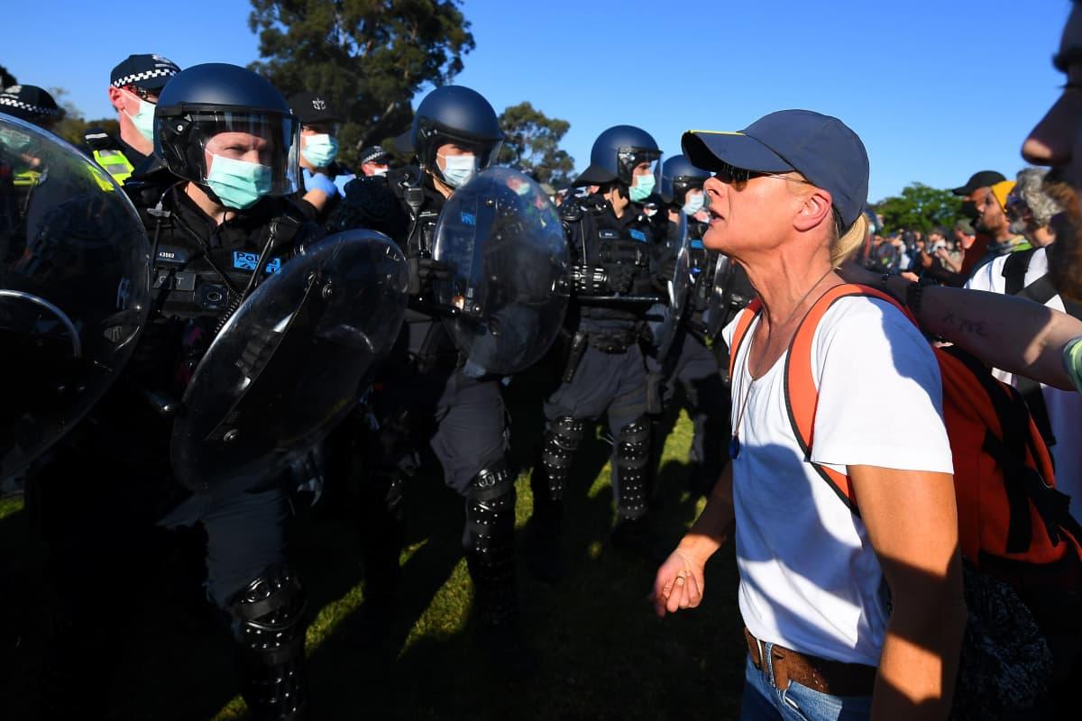 Protestoija huutaa mellakkapoliiseille mielenosoituksessa.