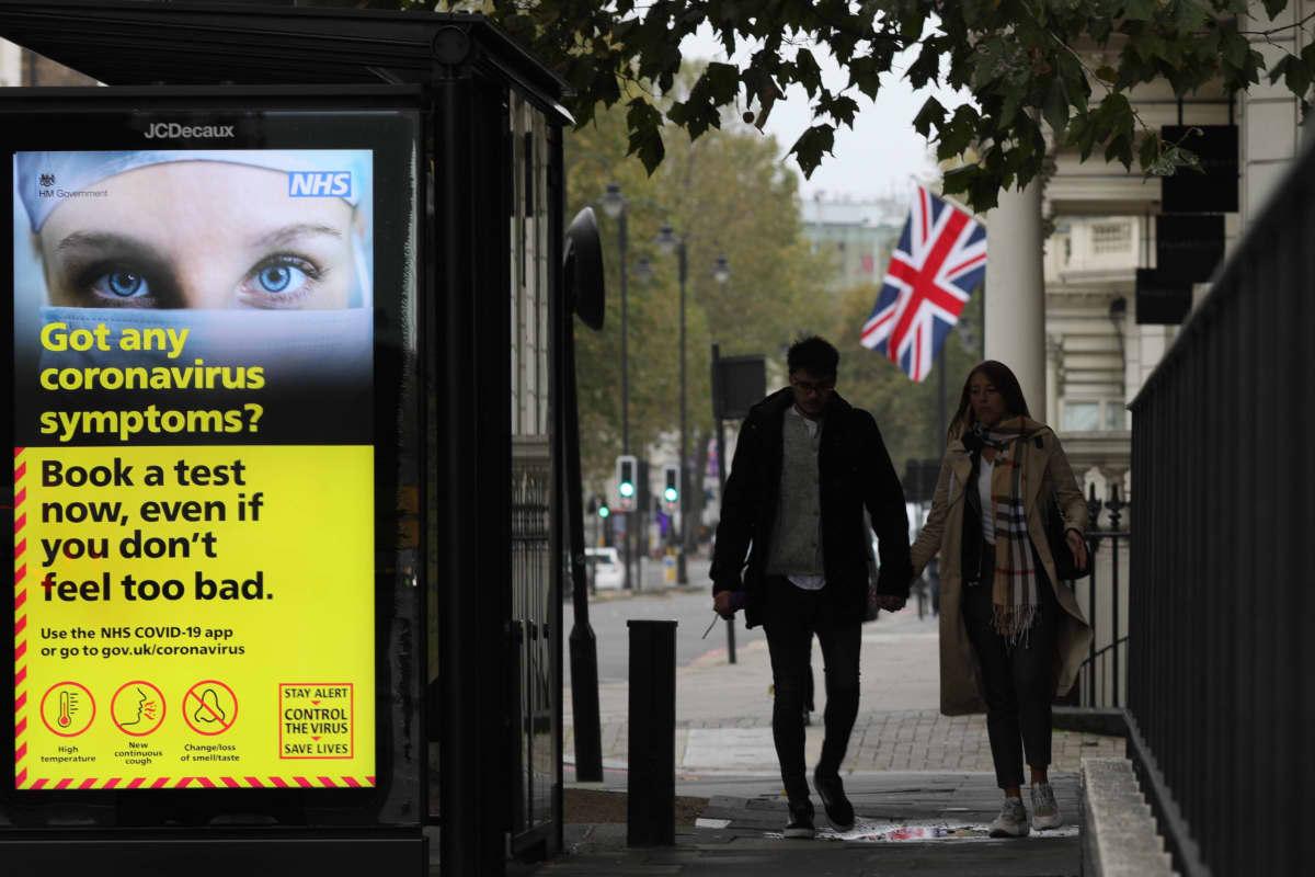 Ihmisiä käveli bussipysäkin ohi Lontoossa 2. marraskuuta 2020. Englanissa ilmoitettiin laajoja rajoitustoimia koronan leviämisen estämiseksi ja ihmisiä pyydettiin pysyttelemään kotona, jos mahdollista kuun alussa.
