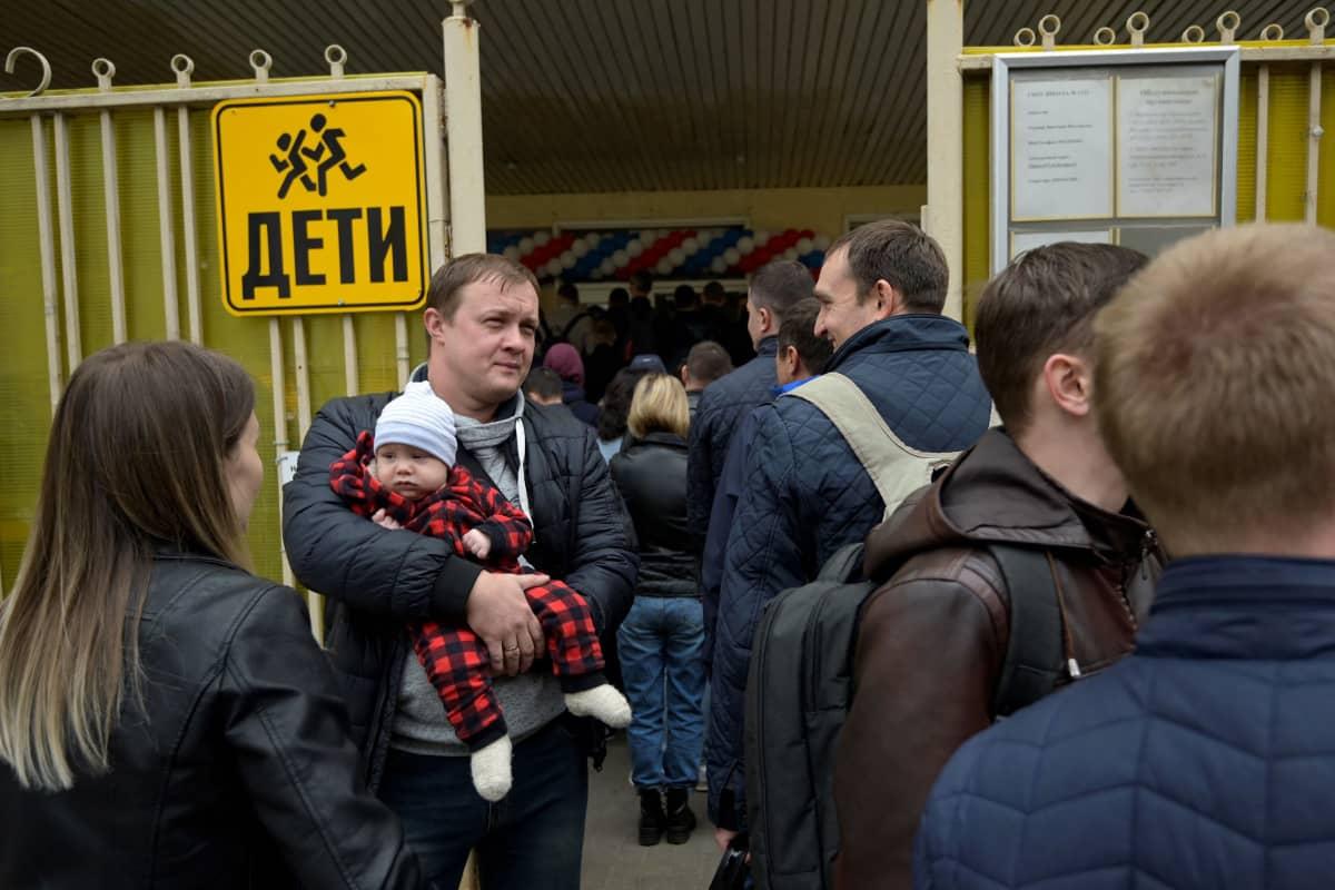 Ihmiset jonottavat äänestyspisteelle, jono jatkuu kadulle asti.