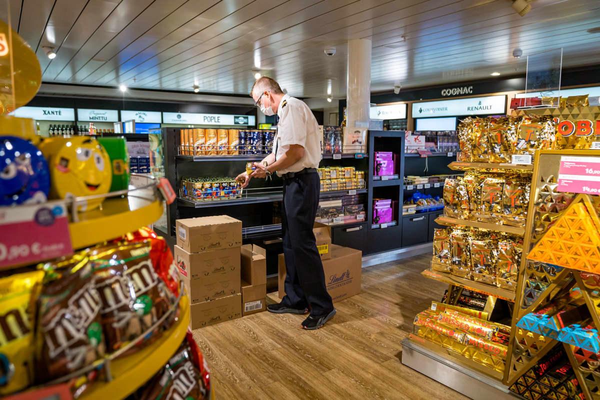 Superstore-kaupan myymäläpäällikkö Niklas Lehtola hyllyttää makeisia.