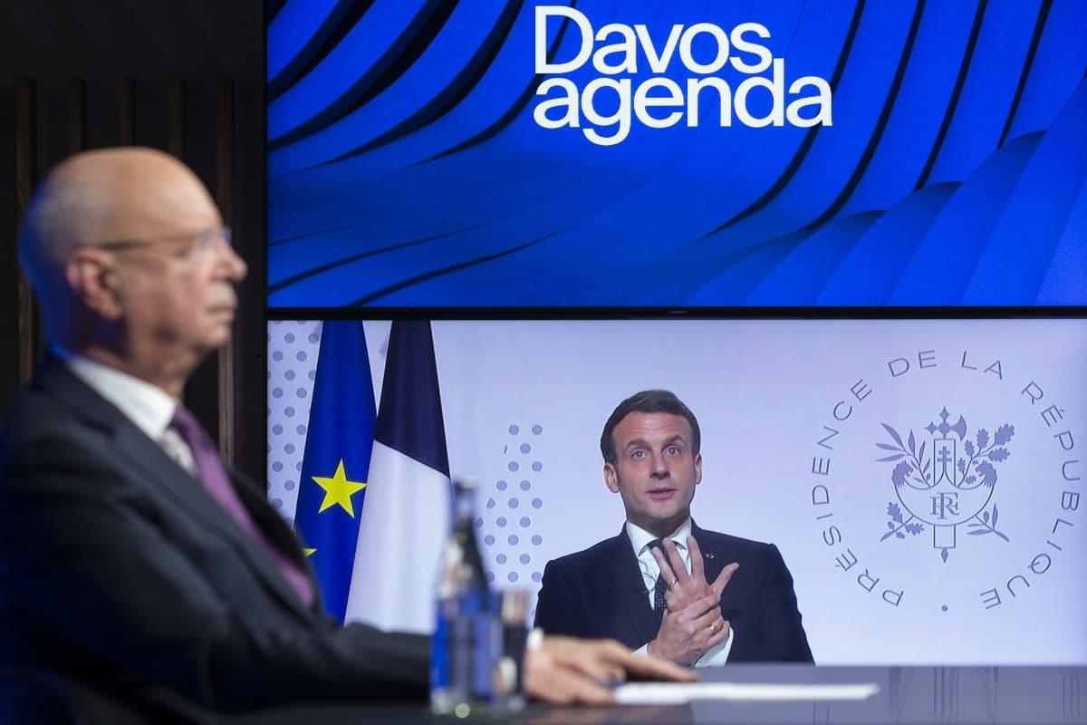 Maailman talousfoorumin puheenjohtaja kuuntelee, kun Ranskan presidentti Emmanuel Macron puhuu ruudulla videokonferenssissa.