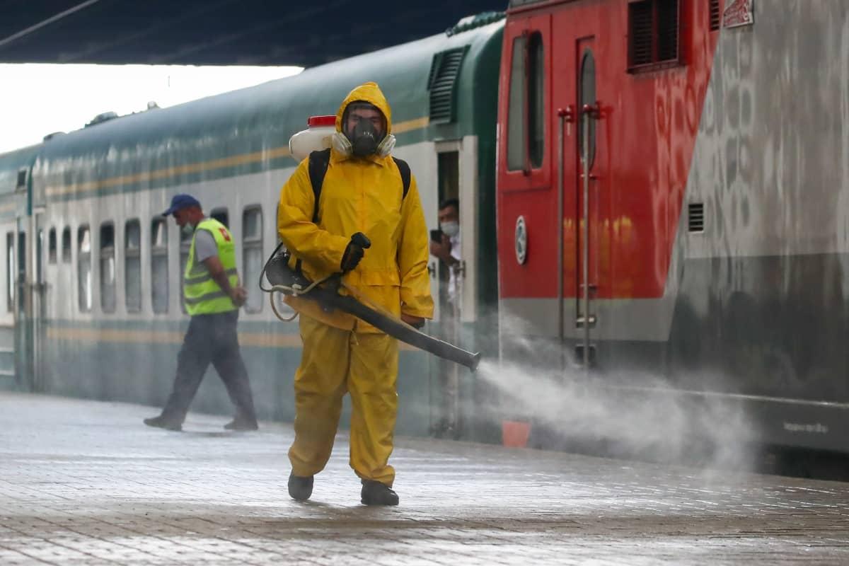 Keltaiseen suoja-asuun ja hengityssuojaimeen pukeutunut mies suihkuttaa asemalaiturille desinfiointiainetta selässään olevasta laitteesta. Taustalla näkyy harmaan ja punaisen väreihin maalattuja junanvaunuja ja keltaisiin huomioliiveihin pukeutunut mies.