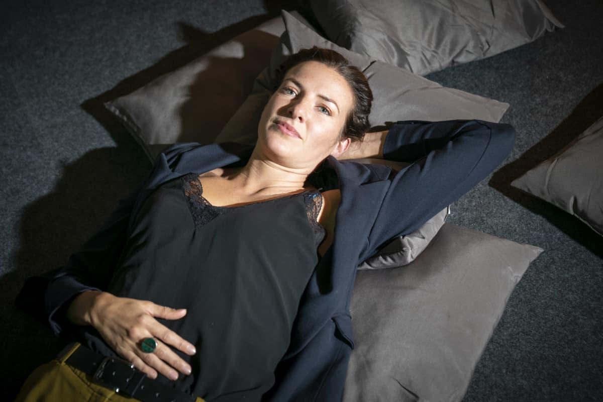 Nainen makaa tyynyjen päällä.