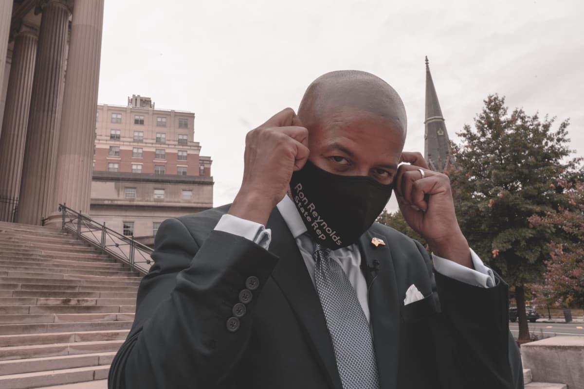 Demokraattiedustaja Ron Reynolds asettelee kasvoilleen maskia.