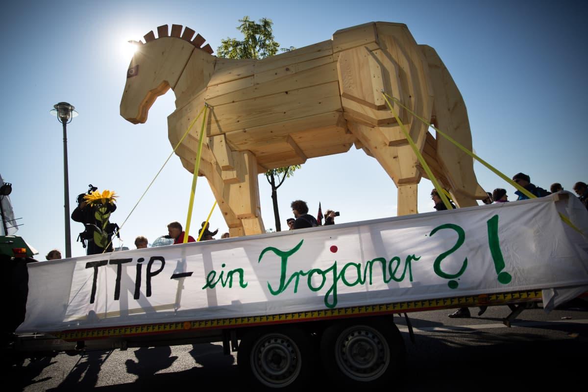 Iso puinen hevonen mielenosoittajien keskellä, plakaatissa teksti: TTIP - Troijan hevonen?!