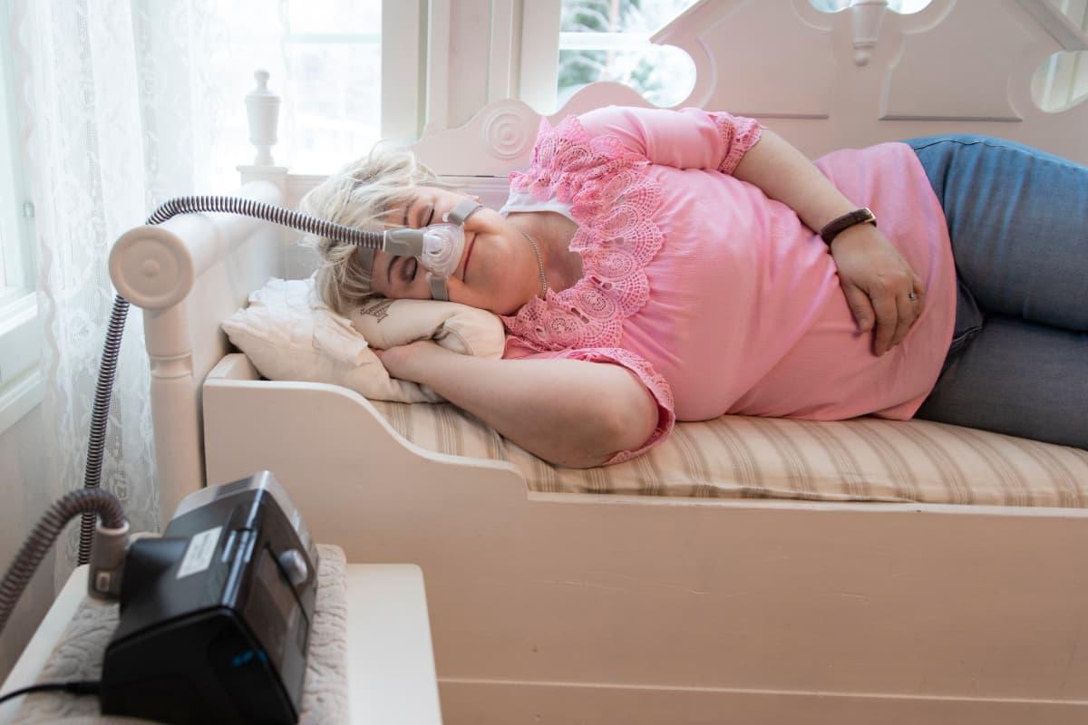 Sari Mäkinen nukkuu päiväunia valkoisella puusohvalla.