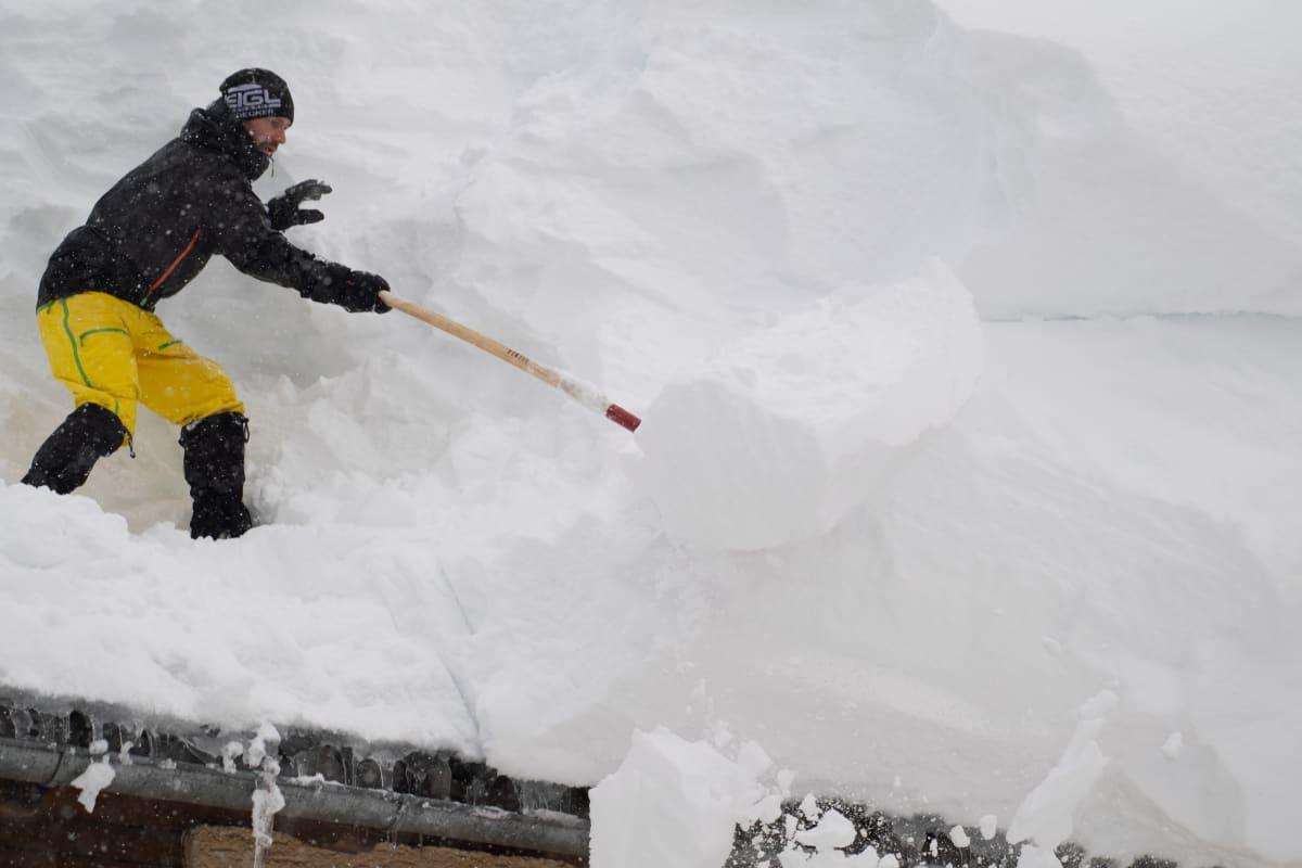 Mies poistaa lunta katolta Itävallan Filzmoosin kaupungissa.
