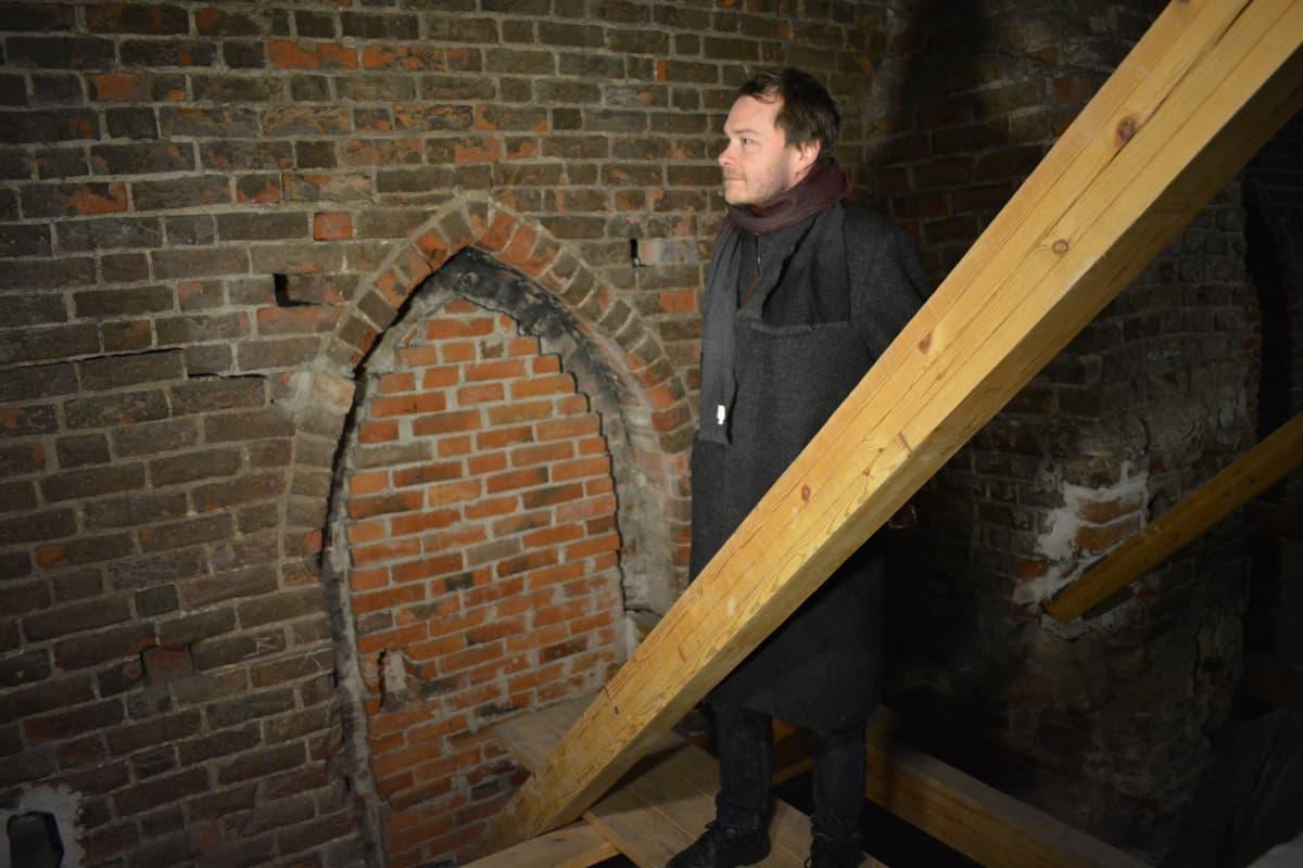 Panu Savolainen katsoo 1300-luvulta peräisin olevaa Turun tuomiokirkon ulkoseinää, joka on laajentuneen kirkon ullakon sisällä.