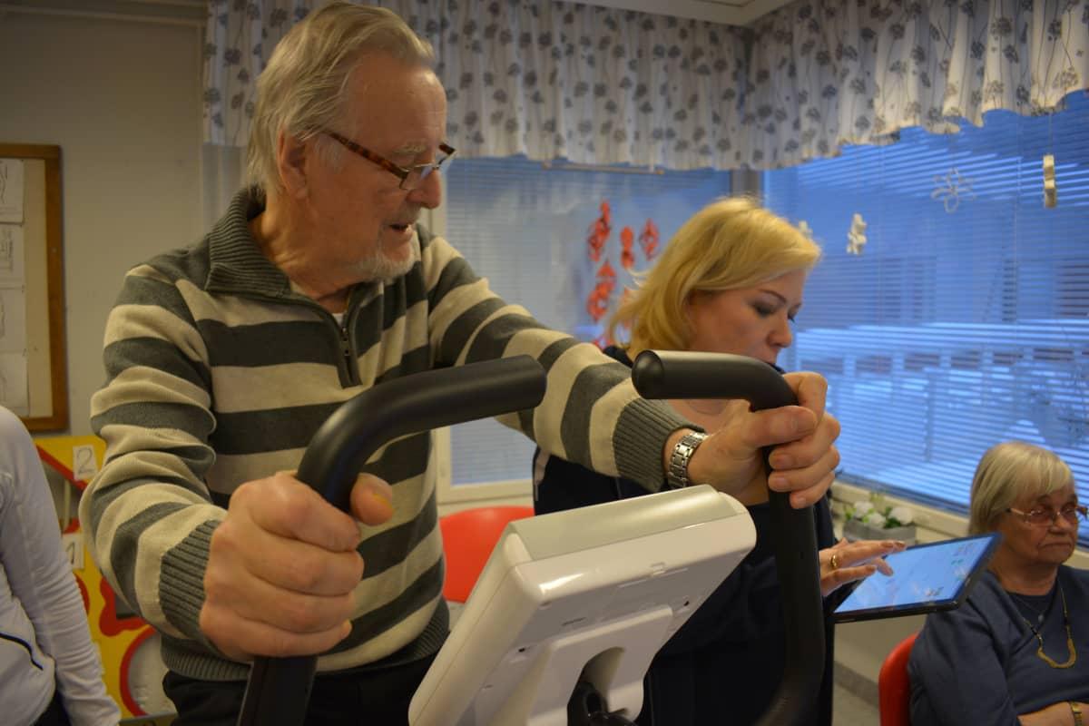 Reino Ilola antaa ohjeita, minne haluaa ajaa. Minna Laine näppäilee osoitteen kartalle. Sen jälkeen reitti avautuu televisioruudulle.
