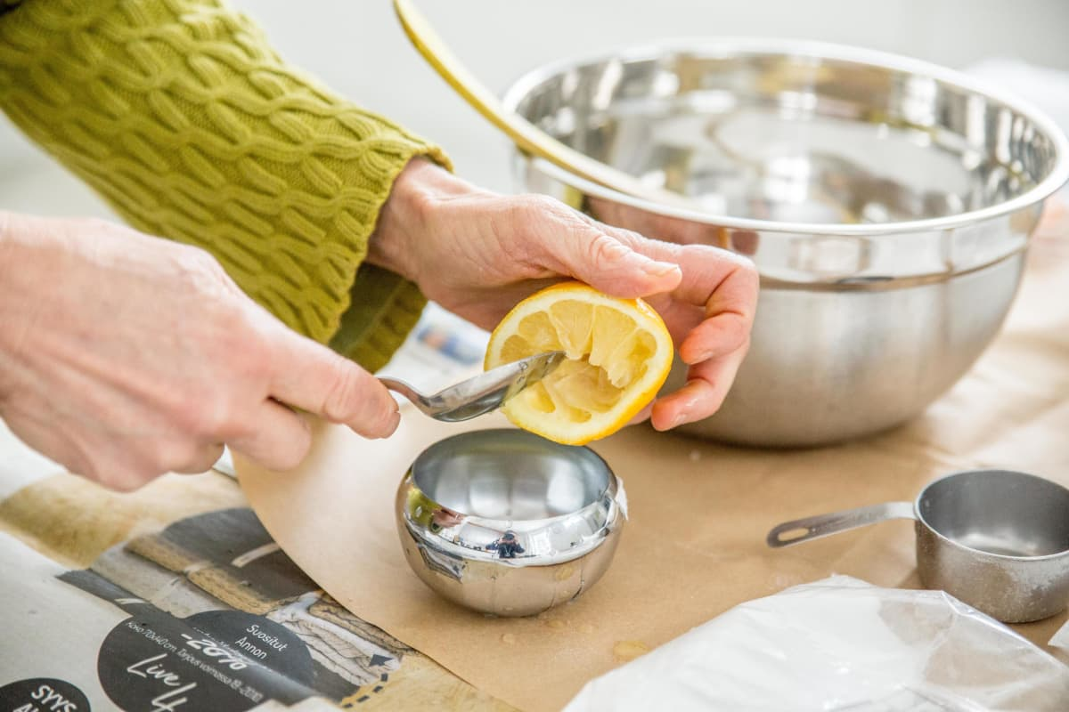 Käsi kaapii lusikalla sitruunasta lihoja