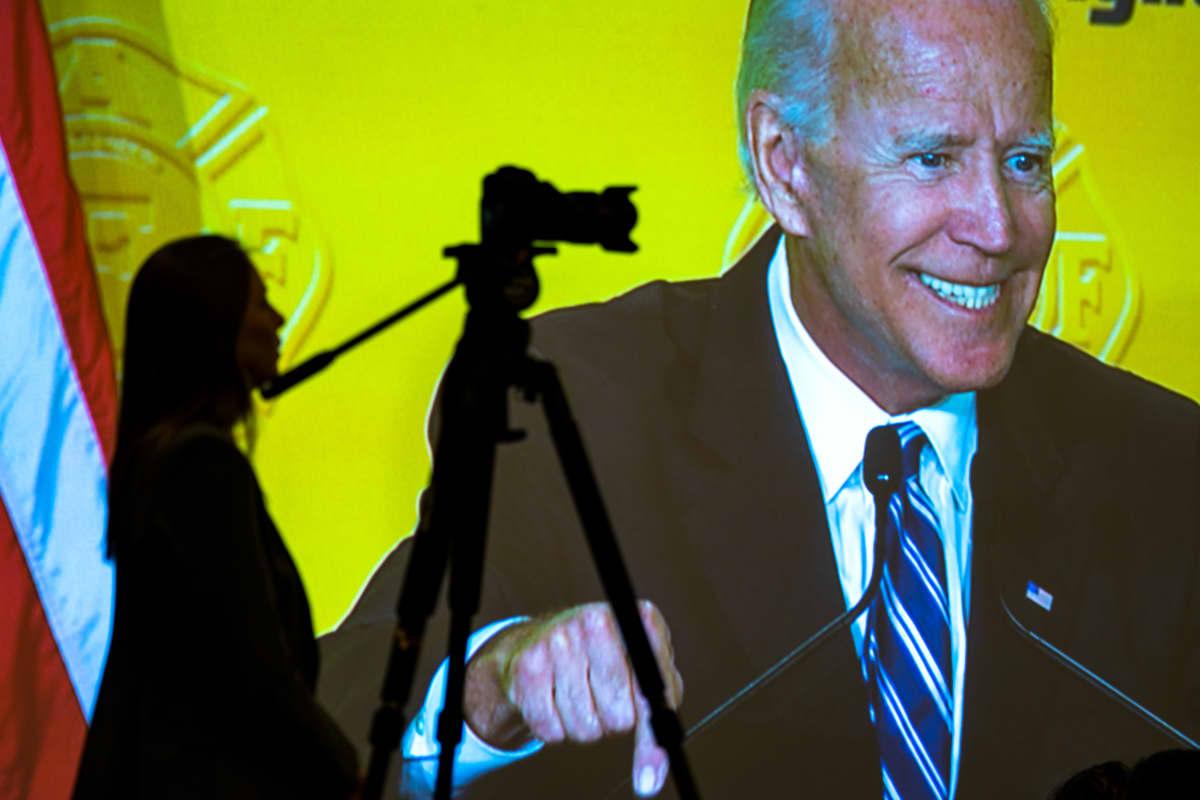 Joe Bidenin kuva heijastettiin valkokankaalle hänen puhuessaan kansalliselle palomiesten yhdistykselle maaliskuussa Washingtonissa.