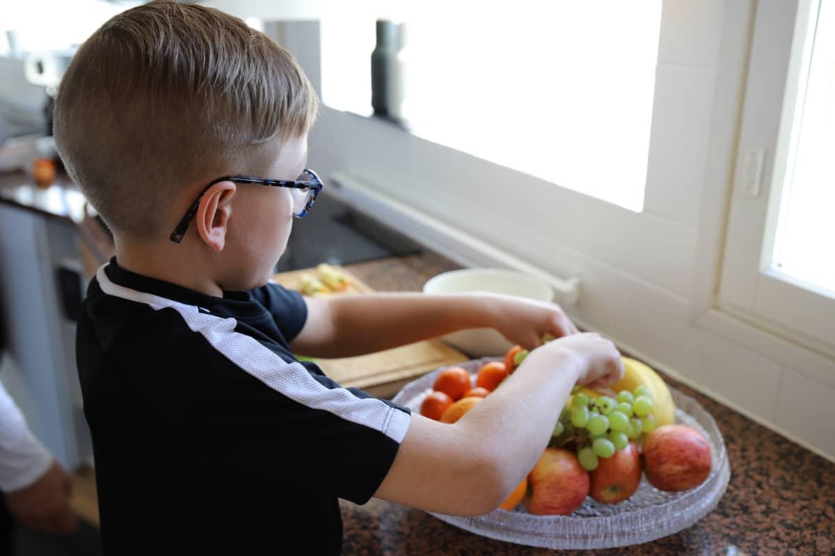 Hermanni Vastamäki tekee hedelmäsalaattia.
