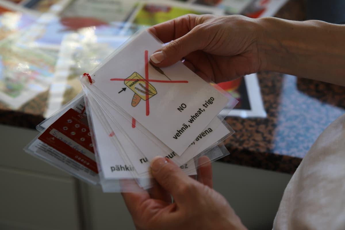 Kortteja, joissa lukee eri kielillä ja näytetään kuvilla tuotteita, joita Hermanni Vastamäki ei voi syödä.