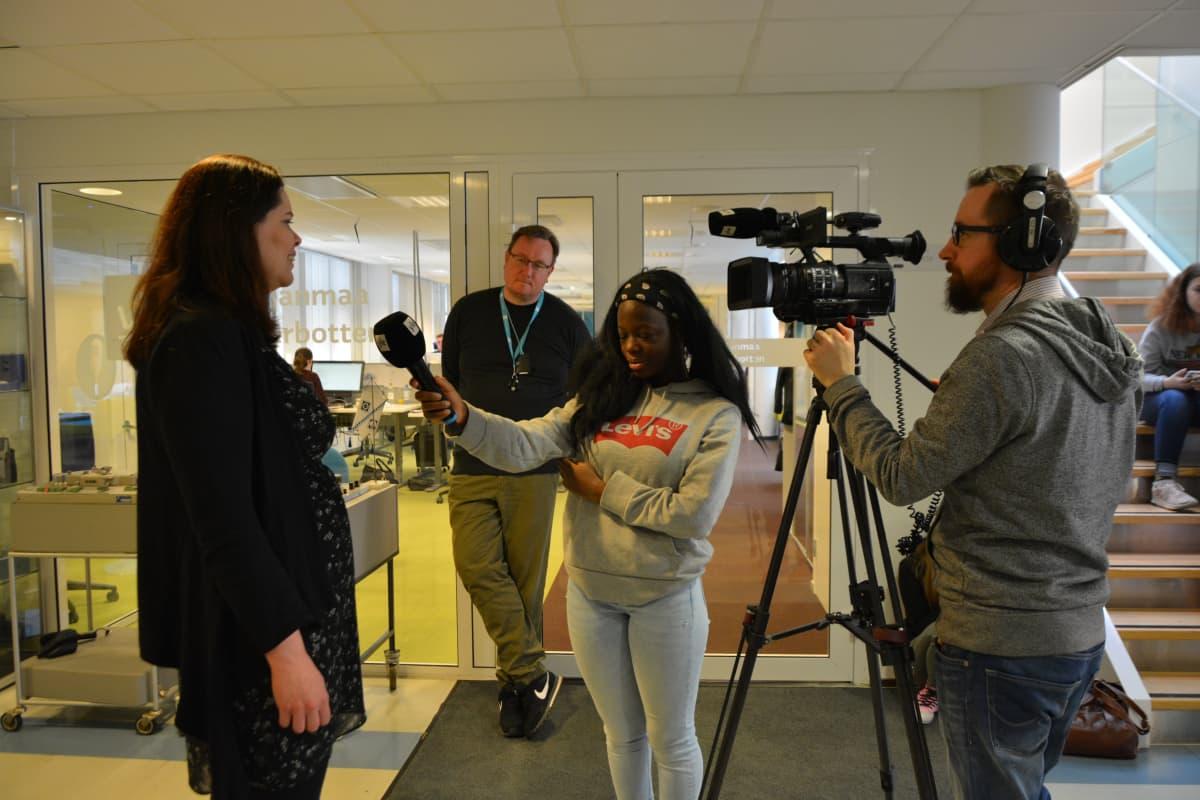 Tilde Muotio haastattelee opettaja Sari Kleemolaa. Uutiskummeina kuvaaja Jarkko Heikkinen ja toimittaja Tuomo Rintamaa.