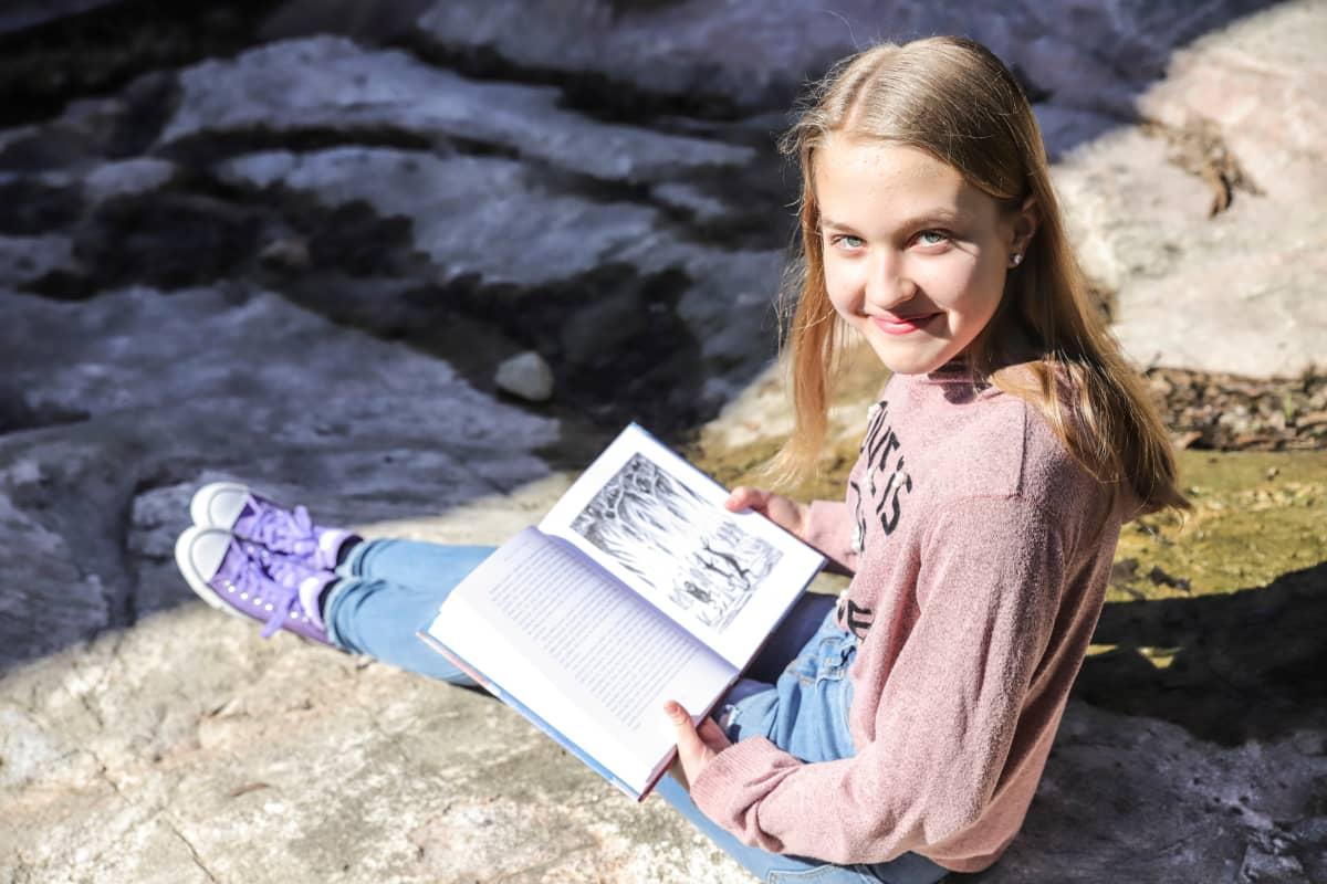 Olivia Lorien Levo istuu ja pitelee Hobitti-kirjaa.
