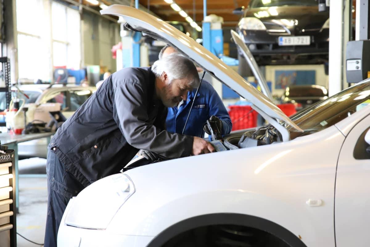 Autoalan opettaja Petri Sällilä tutkii autoa.