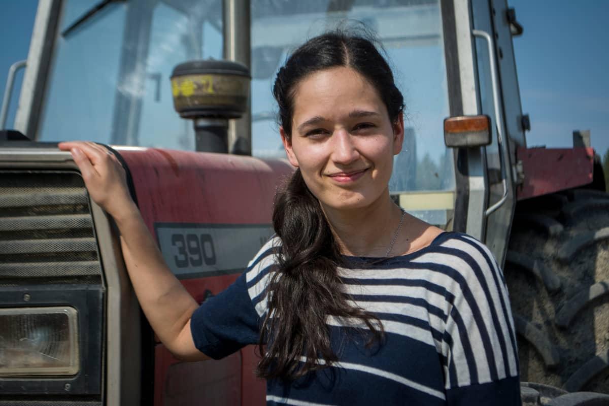 Mikaela seisoo traktorin vieressä maitotilalla.