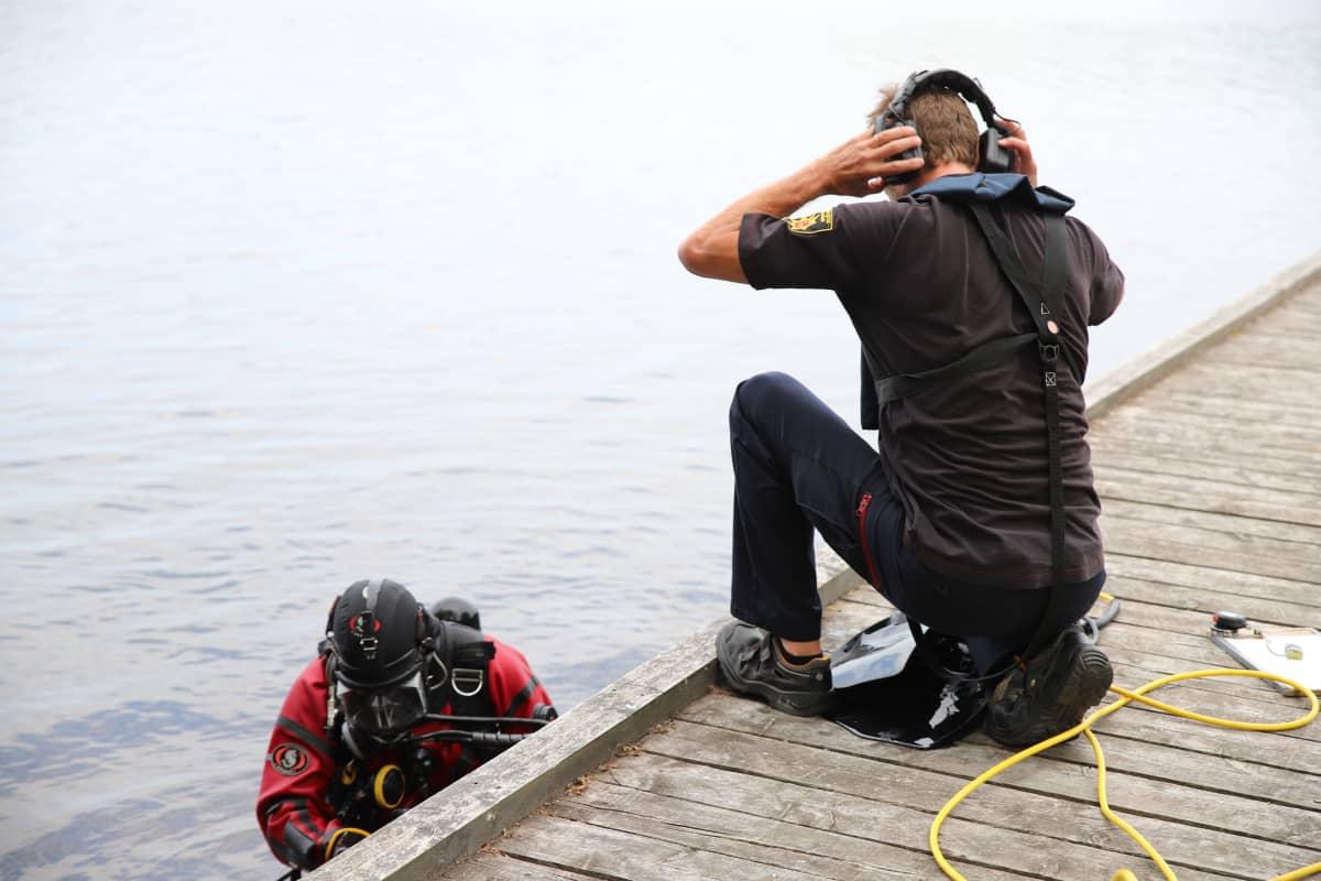 Avustaja laittaa kuulokkeita päähän pitääkseen radioyhteyttä sukeltajaan