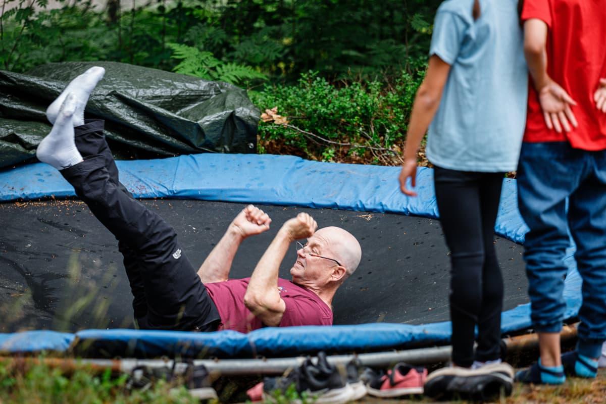 Mies näyttää miten trampoliinilla hypitään selällään