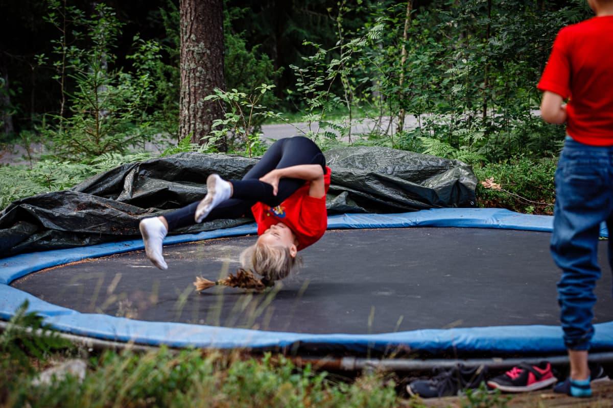 Lapsi tekee kuperkeikkaa trampoliinilla