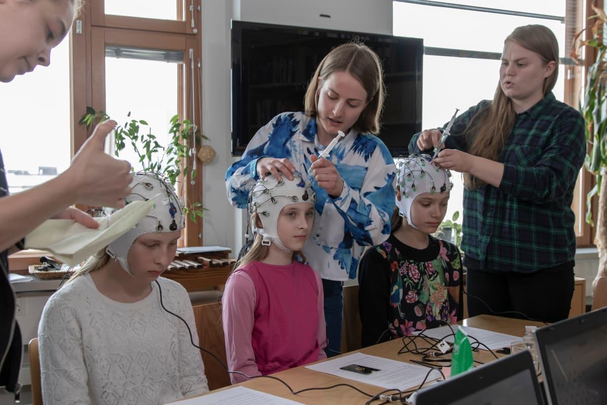 Viidesluokkalaiset Lumi Markkanen (vasemmalla), Taika Granroth ja Martta Murdvee osallistuvat Helsingin yliopiston tutkimukseen, jossa mitataan lasten kykyä keskittyä koulutehtäviin häiriöäänien keskellä.