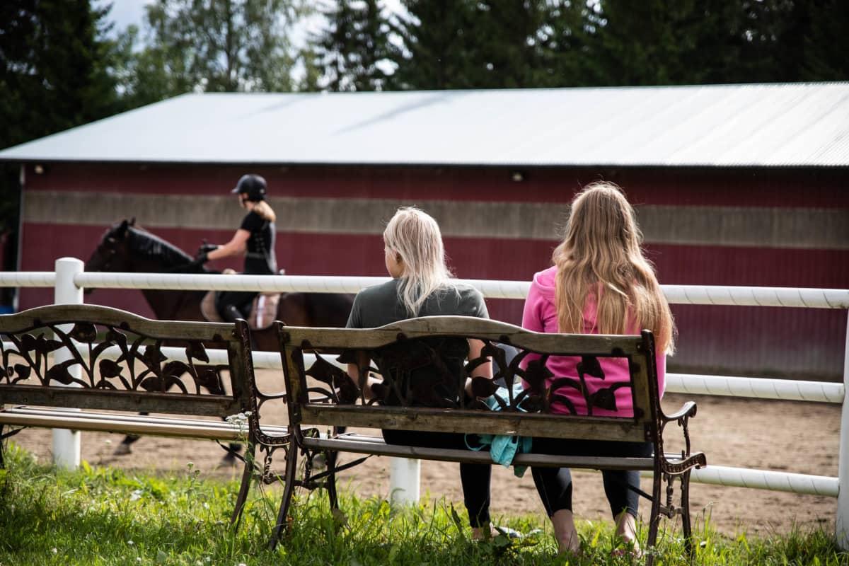 Tytöt katsovat ratsastustuntia kentän sivussa.