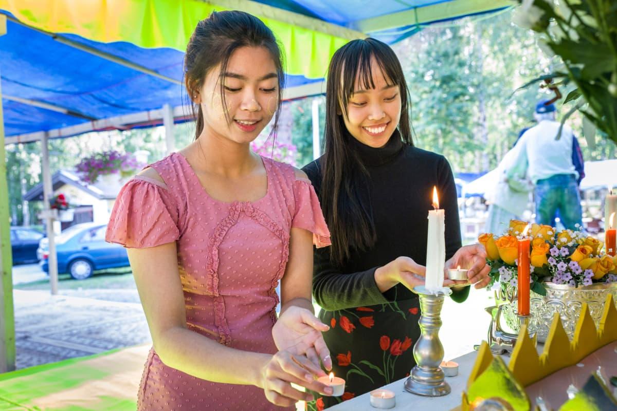 Wine Wine ja Chu Chu Kyaw sytyttävät kynttilöitä