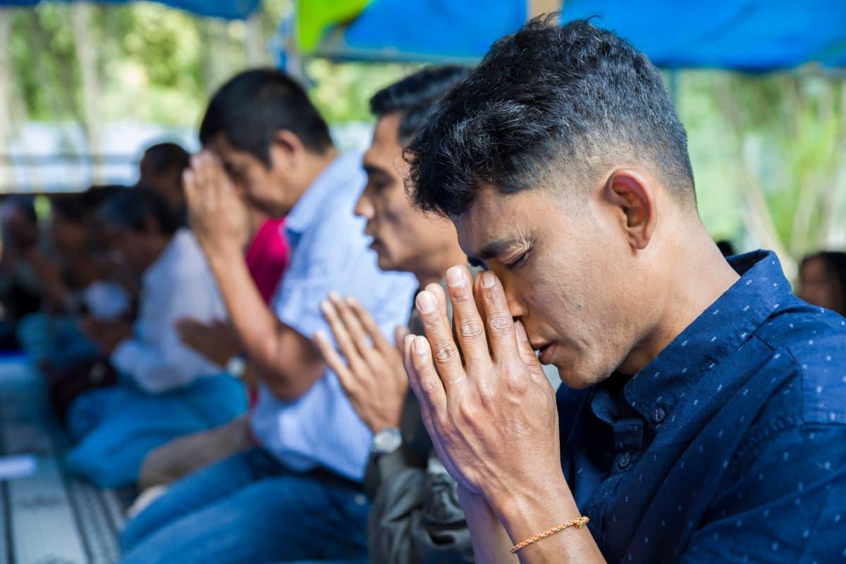Mies rukoilee buddhalaisluostarissa.