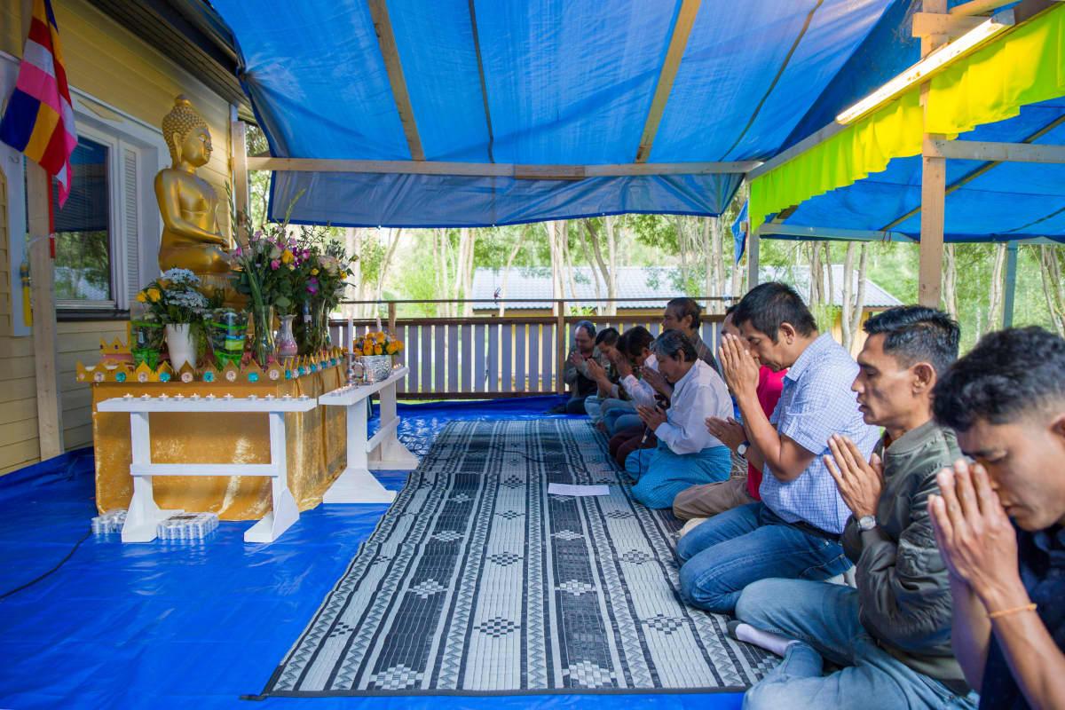 Ihmiset rukoilevat buddhan patsaan edessä.