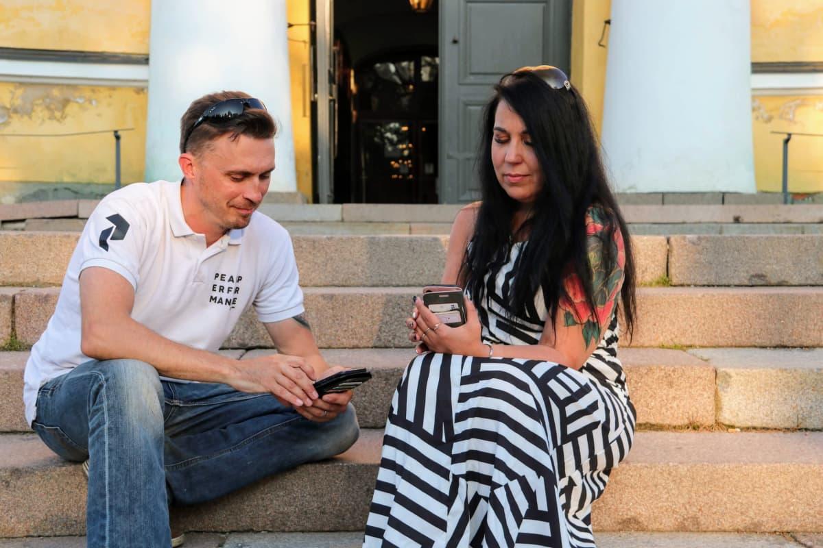 Pariskunta selailee puhelimia kirkon portailla