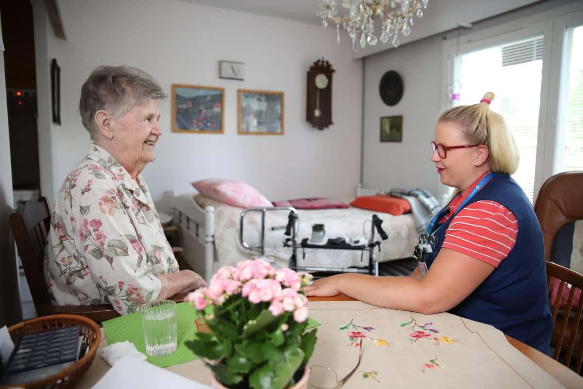 Iäkäs nainen ja hoitaja istuvat saman pöydän ääressä