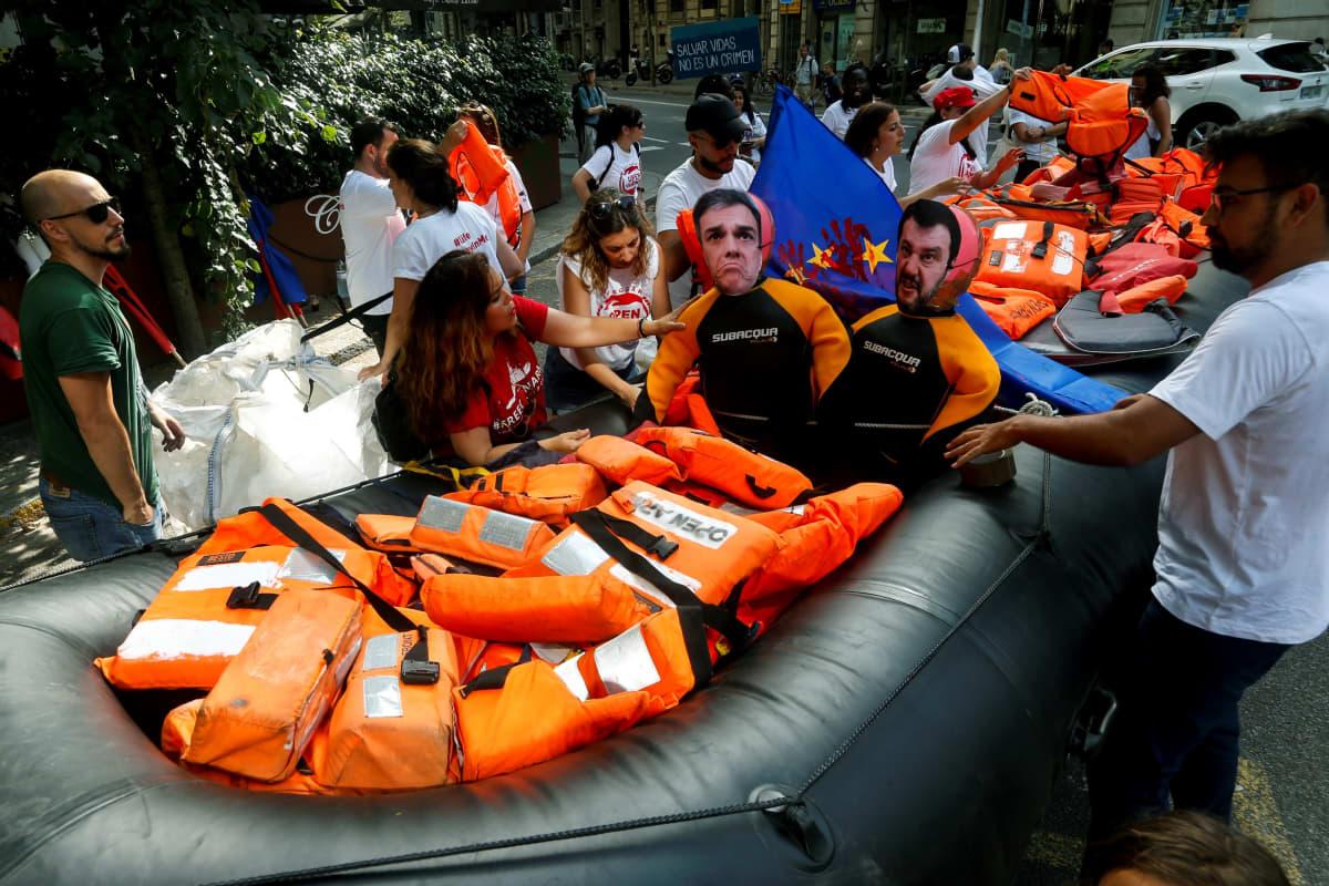 Open Arms protestoi järjestöjen pelastustoiminnan kriminalisointia Barcelonassa heinäkuussa. Kumiveneeseen on asetettu Espanjan vastaavan pääministerin  Pedro Sánchezin ja Italian sisäministerin Matteo Salvinin kuvat.