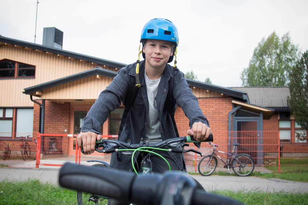 Lassi Laurila polkupyörän selässä Kangasalan Vatialan koulun pihalla.