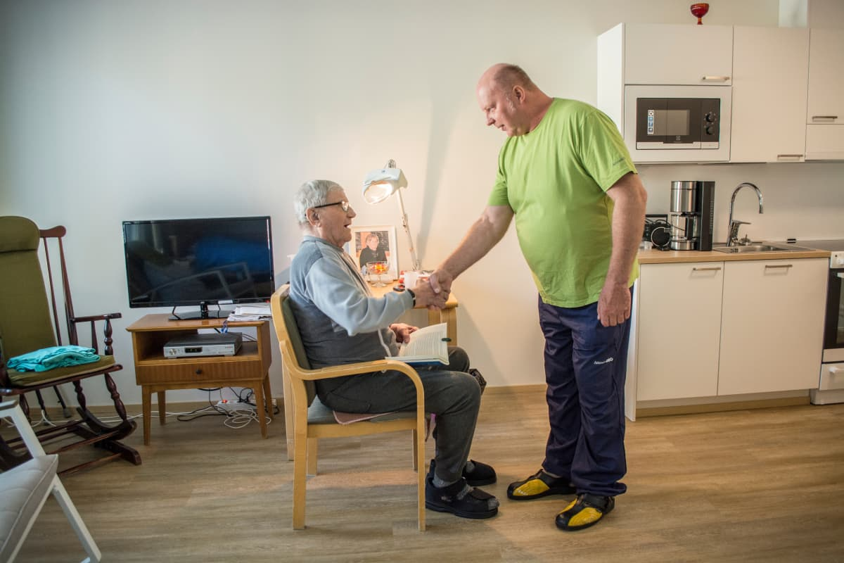 Attendo Vuokon asukas Vilho Mähönen kättelee hoitaja Jouko Kumpulaista.
