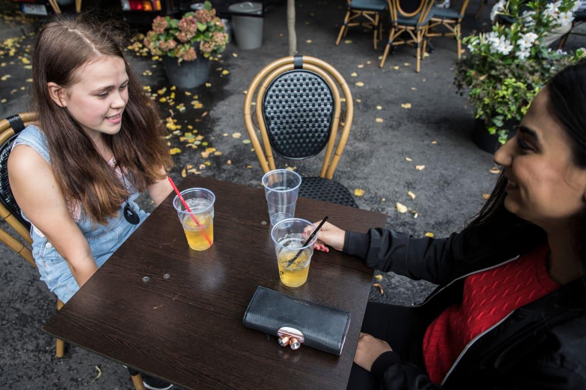 Katariina Räikkönen kahvilassa avustajansa kanssa.