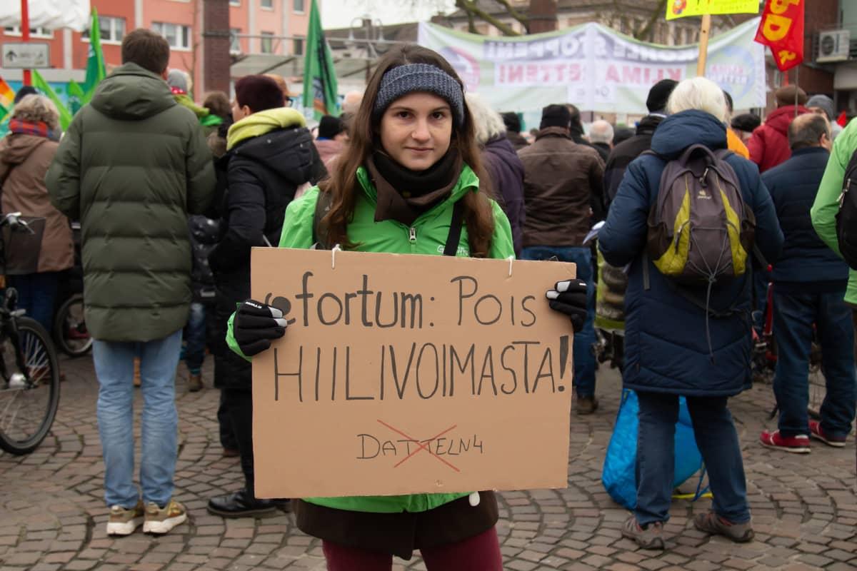 """nainen kyltin kanssa, kyltissä lukee: """"Fortum: pois hiilivoimasta!"""""""