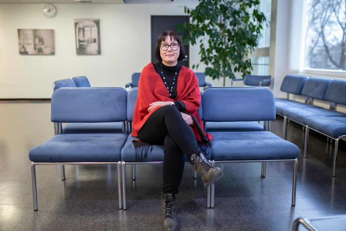 Ilona Rönkkö istuu Hämeenlinnan terveysaseman penkillä.