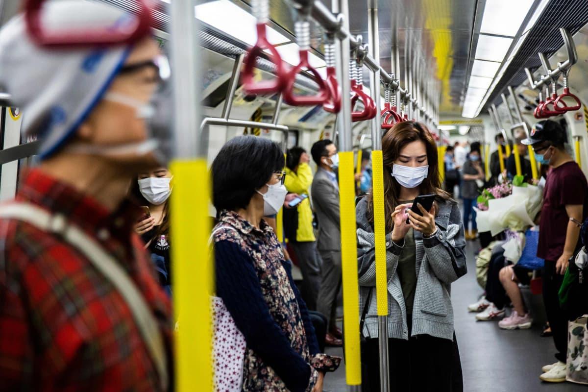 Hengityssuojaimia käyttäviä metromatkustajia Hongkongissa.